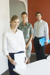 Three businesspeople standing in office with documents