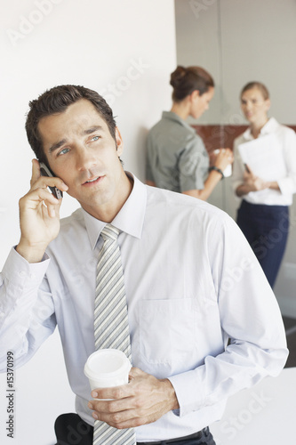 Businessman talking on cell phone with two women in background