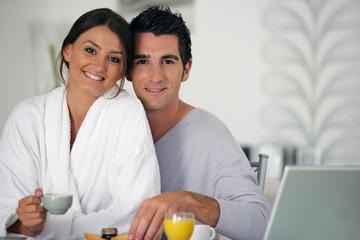 Couple souriant prenant leur petit déjeuner
