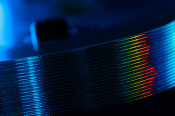 Stack of CD and rainbow reflection. Compact disks in blue light