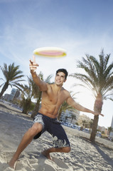 Man in swimsuit playing with flying disc on beach