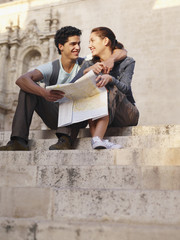 Young tourist couple sitting outdoors on steps in front of old church