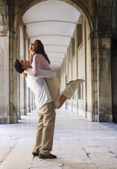 Young couple embracing in an old European colonnade