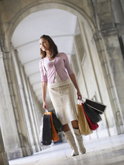 Woman with shopping bags walking in an old European colonnade