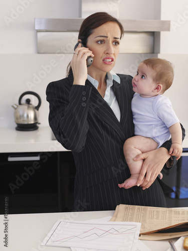Mother holding baby daughter while talking on phone in kitchen