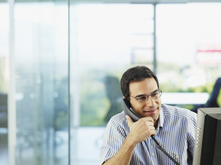 Man in office talking on telephone