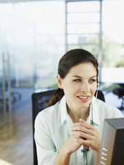 Woman in office talking on telephone headset