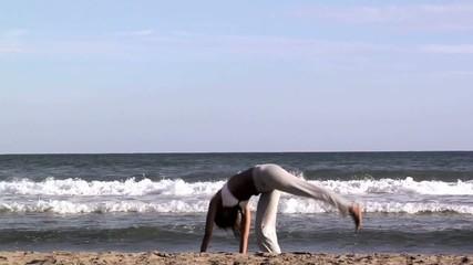 Donna esegue la ruota sulla spiaggia