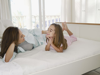 Mother lying on bed with young daughter