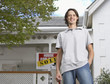 Man with keys standing in front of house with sold sign