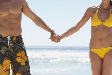 Man and woman in swimsuits holding hands outdoors