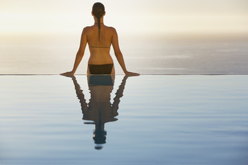 Woman sitting on edge of infinity pool in bikini