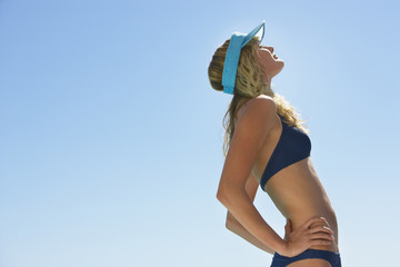 Woman in bikini and visor outdoors stretching