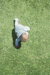 Aerial view of baby crawling on grass