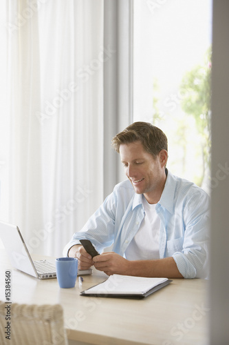 Man with laptop and cell phone at home smiling