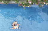 Mother with baby in pool with flowers