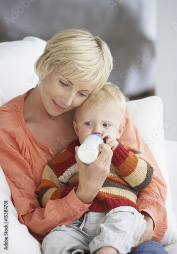 Woman feeding baby boy with bottle