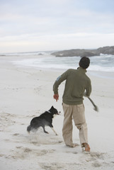 Man on beach throwing stick for dog