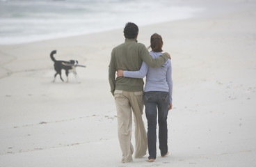 Man and woman on beach with dog