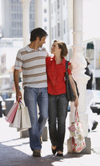 Man and woman walking outdoors with shopping bags