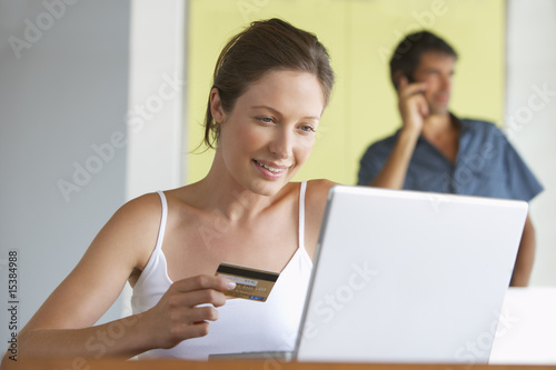 Man and woman with credit card at laptop