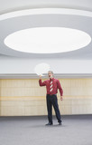 Businessman with word balloon under ceiling light