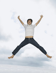 Man leaping outdoors with clouds and trees