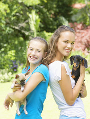 Two teenage girls with puppy dogs