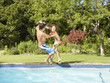 Teenage boy and girl falling into pool