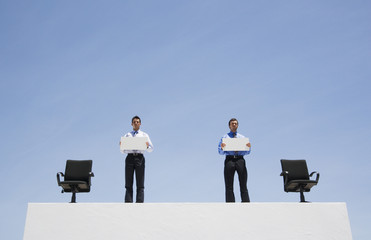 Two businessmen on wall with office chairs and blank signs