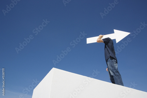 Man outdoors on wall with blank arrow