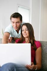 homme et  femme souriants devant un ordinateur portable