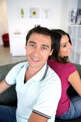 homme et femme souriants assis dos à dos sur un canapé
