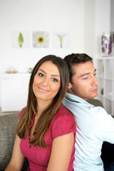 homme et femme souriante assis dos à dos sur un canapé