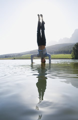 Man doing handstand on water