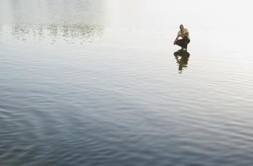 Man crouching on water