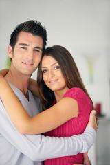 Portrait d'un jeune couple souriants s'enlaçant