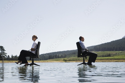 Businessman and woman in office chairs on water facing away