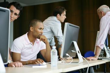 Portrait d'un homme métis au bureau devant un ordinateur