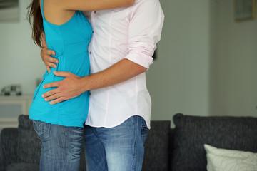 Jeune couple s'enlaçant dans un salon