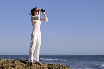 Frau mit Fernglas auf einem Felsen