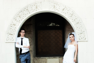 Bride and groom standing under white carved arch