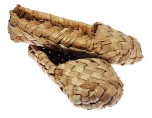 Old Russian sandals made of bark on a white background