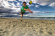 Man is jumping for a volleyball on a beach