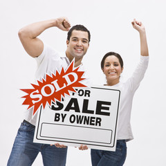 Couple with FSBO home sold sign.