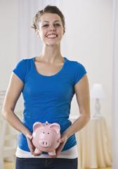 Beautiful woman holding piggy bank.