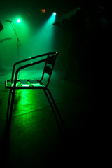 Chair on the stage in green backlight with a fiddler