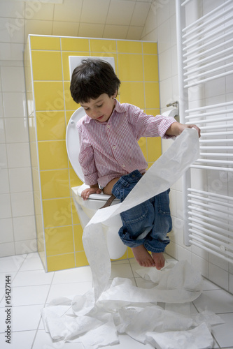 Little boy is making a mess with toiletpaper