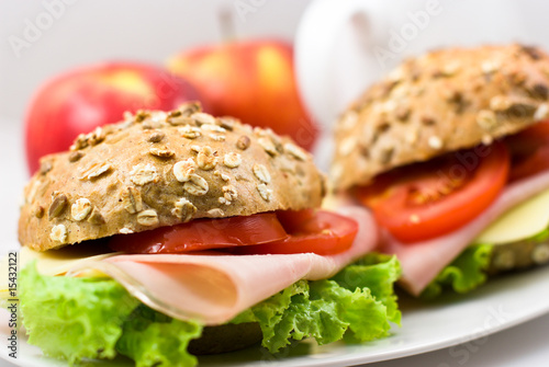 Close up of two sandwiches with ham and vegetables