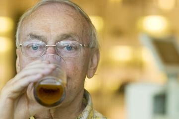 Senior old man drinking half pint beer